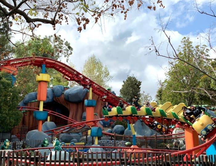 Red roller coaster track with bright yellow coaster and green doors carrying people around a curve