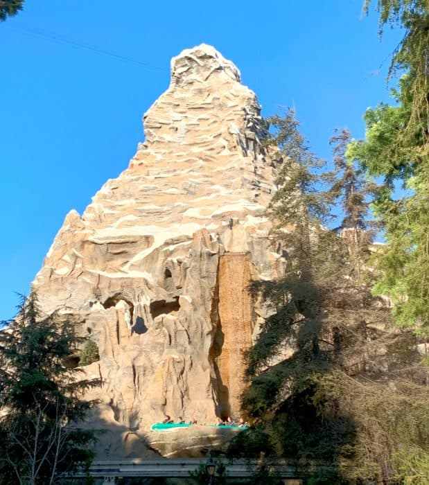 Tall man made rock structure against clear blue sky with several green pine trees in front and a turquoise toboggan carrying people circling the mountain