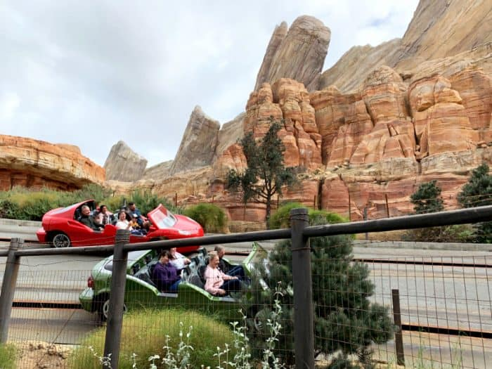 One red car with people in it and one green car with people in it race around a track in front of orange rock mountains