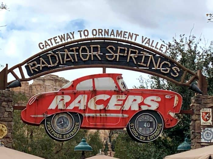 Red steel sign car with white letters spelling RACERS under a brown wooden sign that reads Radiator Springs