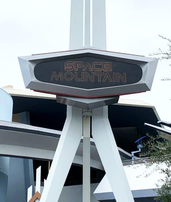 Tall white Space Mountain Sign against a gray sky