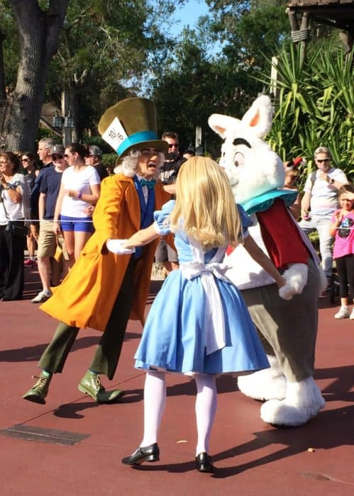 Alice in Wonderland wearing her blue and white dress, the Mad Hatter in a bright yellow long jacket with huge top hat and the White Rabbit holding hands in a circle dancing between floats in Disney's Festival of Fantasy parade route.