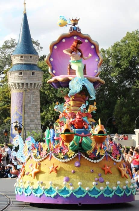 Brightly colored float on Disney's Festival of Fantasy Parade route decorated with vivid yellow, orange, green and purple under the sea elements. At the top is a purple and gold clamshell with Princess Ariel waving to the crowd.