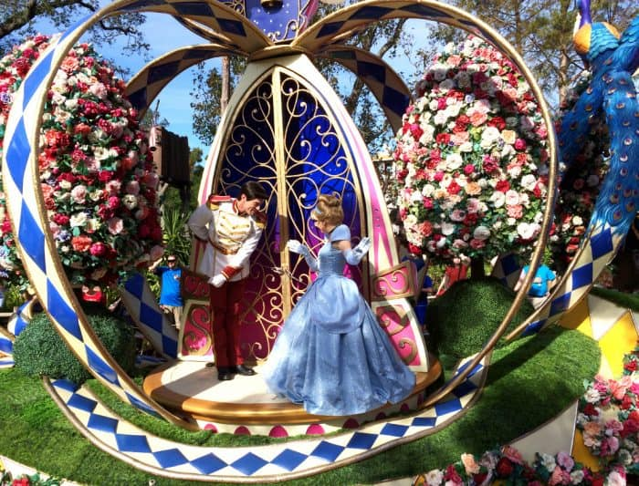 Cinderella in her blue ball gown with Prince Charming in an open air pumpkin carriage decorated with blue chevrons and white background glide on a float in Disney's Festival of Fantasy parade route surrounded by pink, red and white flowers.
