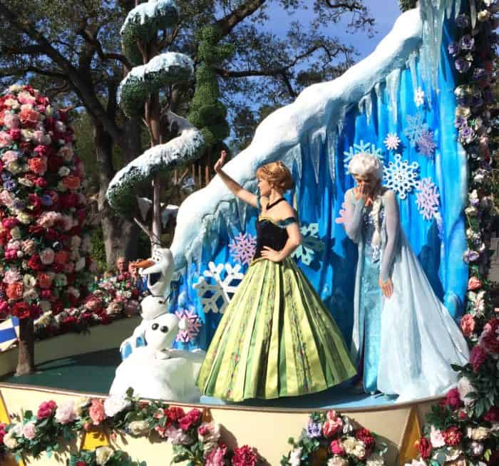 Frozen's Anna and Elsa wave to the crowd on a float symbolizing Arendale and their icy adventures with frozen water and snowflakes. An immovable Olaf stands next to them surrounded by hundreds of red, pink and white flowers on the float during Disney's Festival of Fantasy parade route.