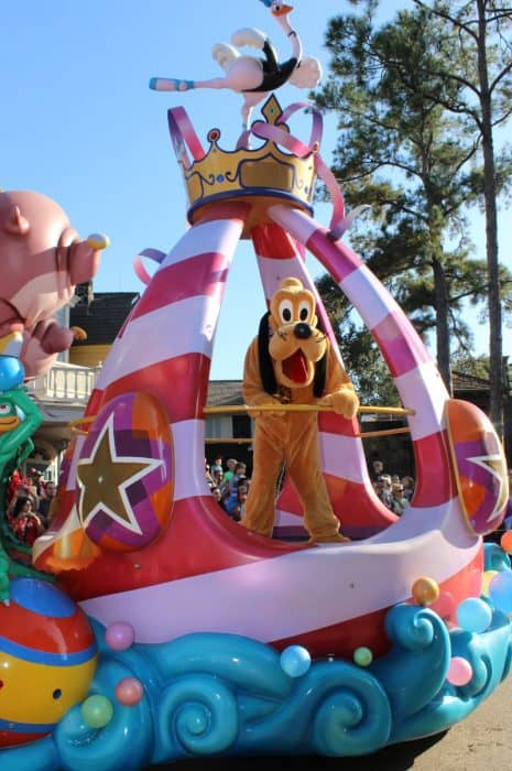 Disney's Pluto - costume tan dog with long black ears, is riding on a red and violet float on Disney's Festival of Fantasy parade route.