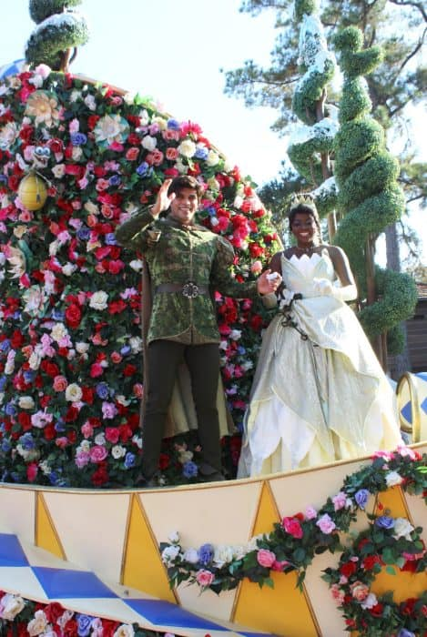 Princess Tiana in a lime green long ball gown and her prince ride on a float with hundreds of red, pink and white flowers in Disney's Festival of Fantasy Parade route.