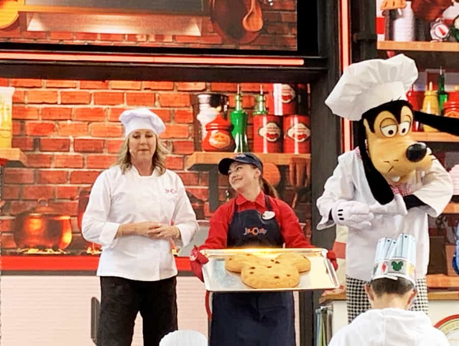 Lady in chef uniform, woman in red shirt and blue apron holding a baked Mickey head cookie with Goofy dressed in chef attire next to her