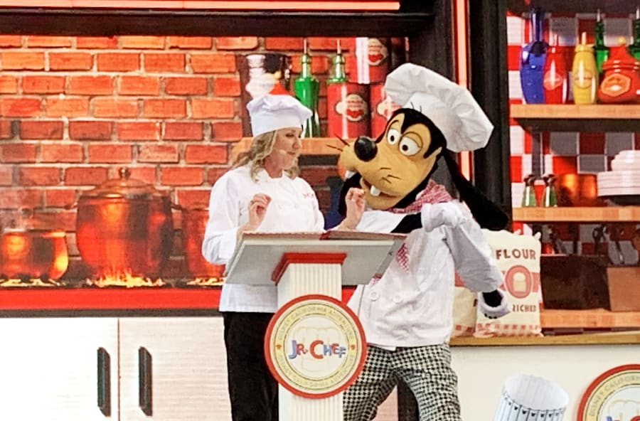 Lady in white chef uniform standing in front of a podium that says 'Jr Chef' and Chef Goofy standing next to her