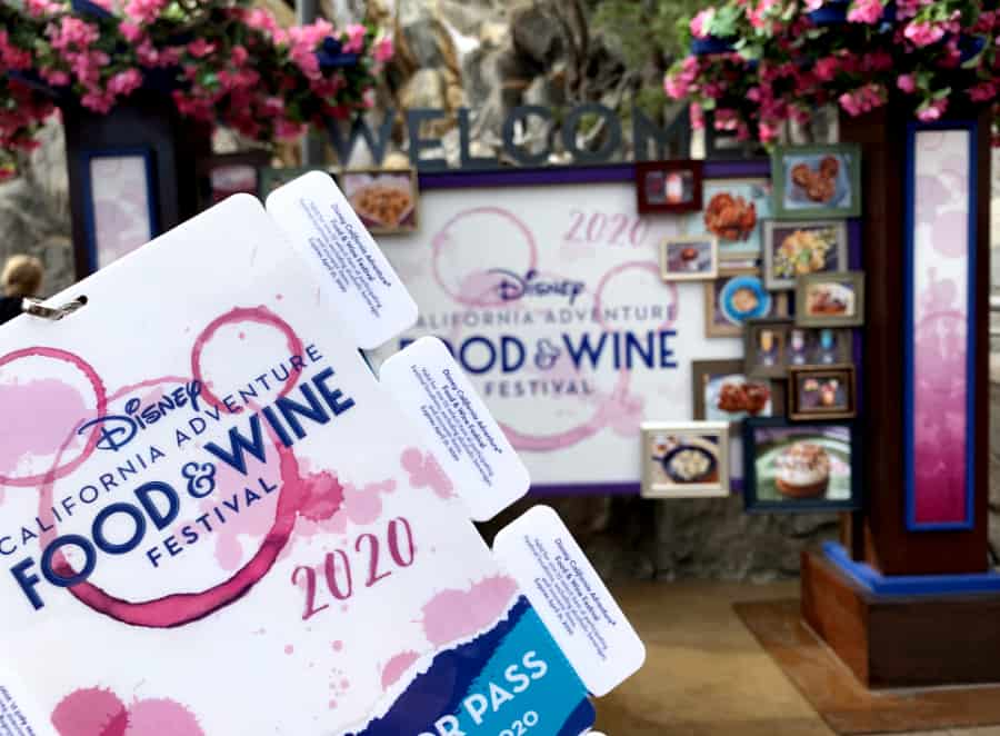 Foreground with California Adventure Food & Wine festival pass with white coupon tabs against a background of pictures of food in frames and dark pink flowers