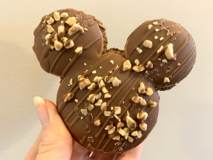 Large Mickey head shaped chocolate macaron cookie with peanuts on top drizzled with more chocolate icing