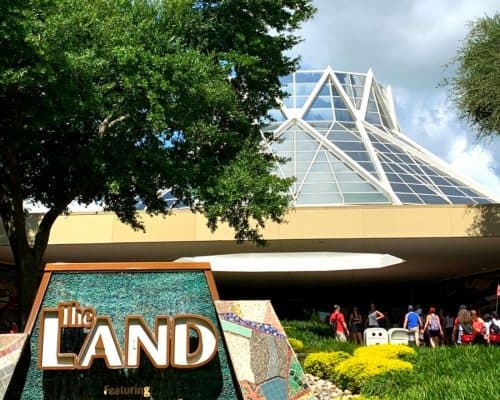 White building in background with tall green tree on the left over . gray sign with white lettering saying The Land with Soarin'