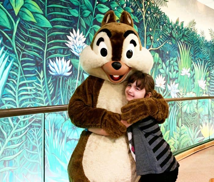 Little girl in gray hugging a big brown and beige costumed chipmunk.