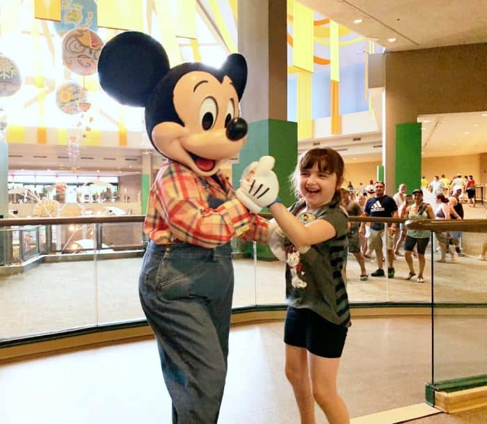 Mickey mouse dressed in denim overalls dancing with a little girl in gray and black in front of a glass railway.