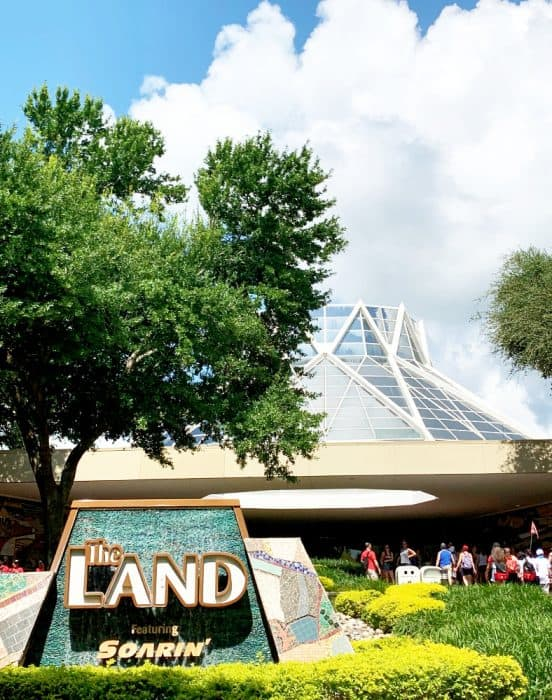 White building in background with a tall tree on the left and a sign in front that reads The Land featuring Soarin'