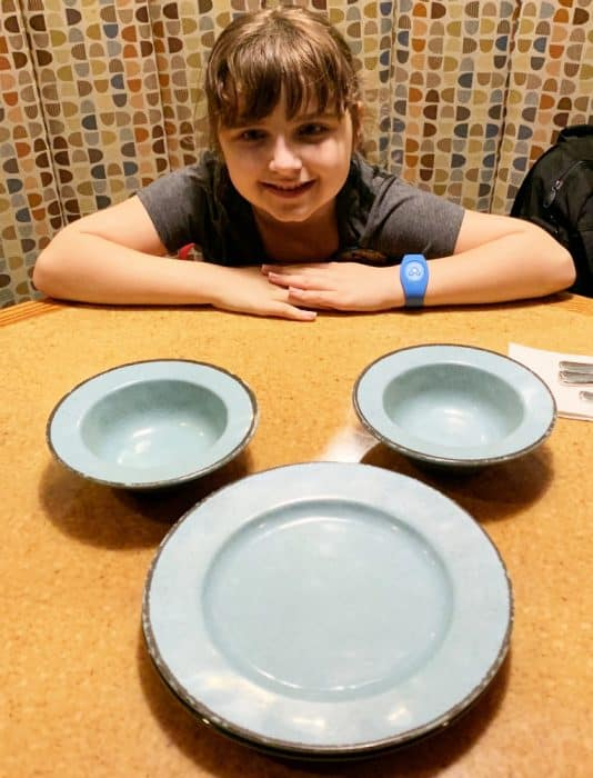 Blue plate and two bowls on a table with a little girl smiling behind it