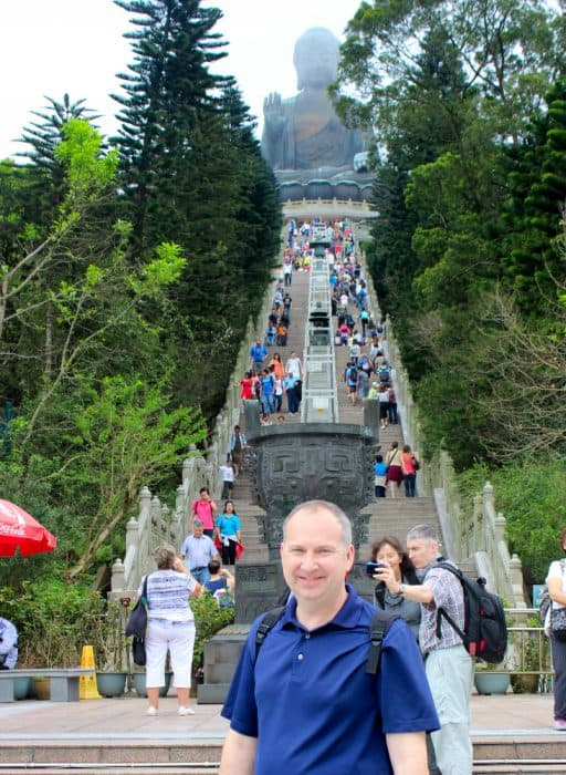 Man in front of step concrete steps leading to a huge bronze Buddha on the hilltop