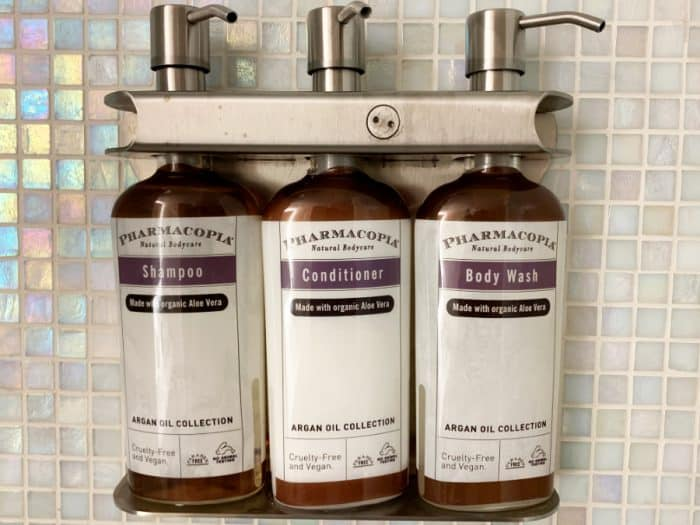Three amber colored bottles of shampoo, conditioner and body wash with white labels attached to a shower wall