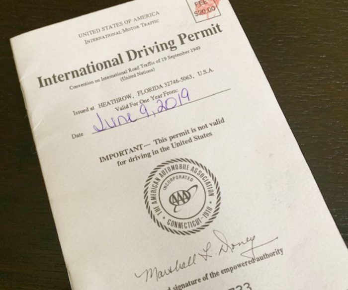 Cream colored booklet with black typing and blue printing with the words International Driving Permit on top of brown table