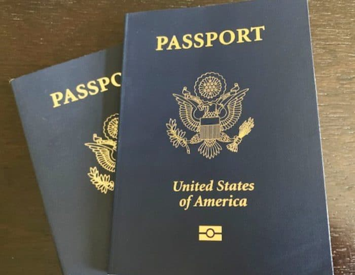 Two blue books with gold writing and emblem saying Passport United States of America on top of brown table
