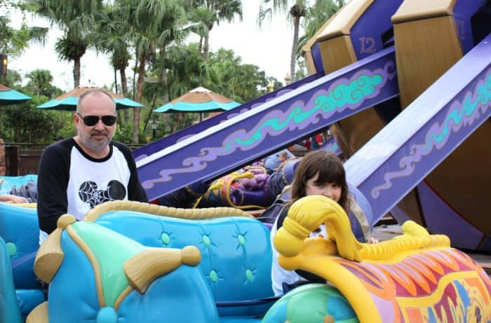 Turquoise and Purple magic carpet ride at Disney with man and child sitting on the ride.