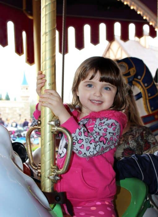 Little girl holding onto a gold pole attached to a white horse statue on the Carousel ride in Fantasyland at Magic Kingdom.