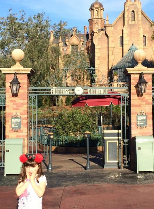 Little girl making face at camera and holding her cheeks in front of the Haunted Mansion Fastpass entrance at Magic Kingdom