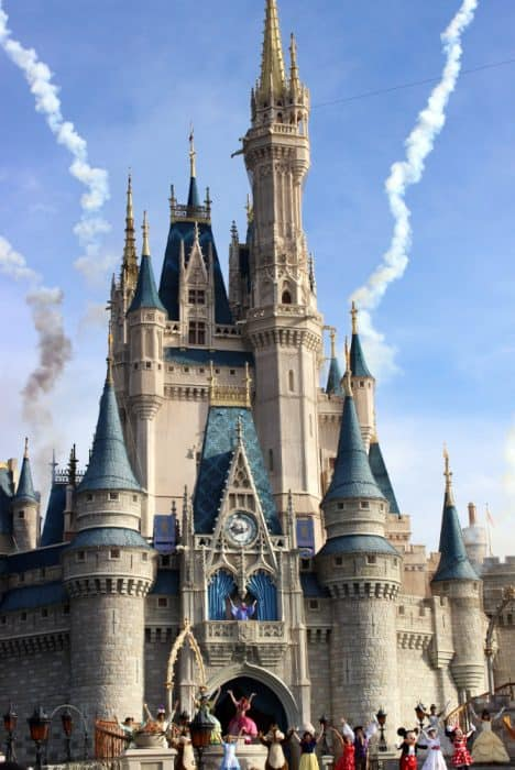 Cinderella's castle at Disney World with fireworks behind the castle with the Welcome show characters; LIght blue sky