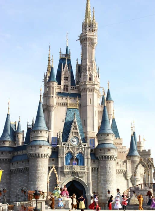 Blue and gray castle against light blue sky with Disney characters dancing in front