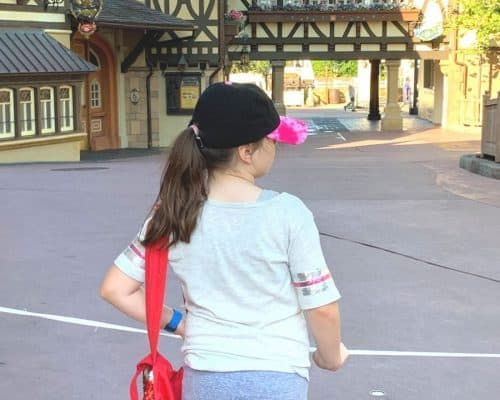 Little girl in gray clothes and red bag in front of a white rope waiting to enter Magic Kingdom.