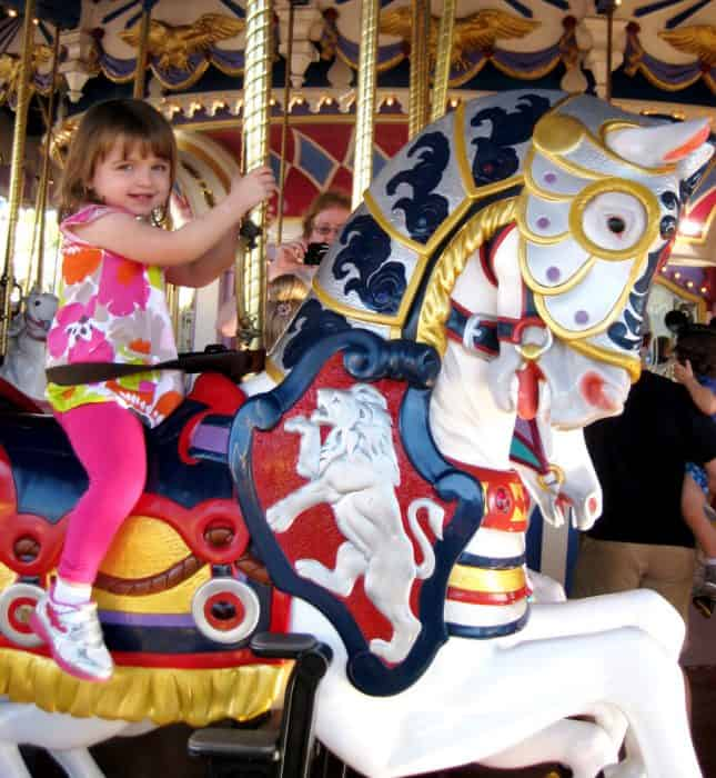 Toddler dressed in pink riding a horse on the carrousel at Magic Kingdom