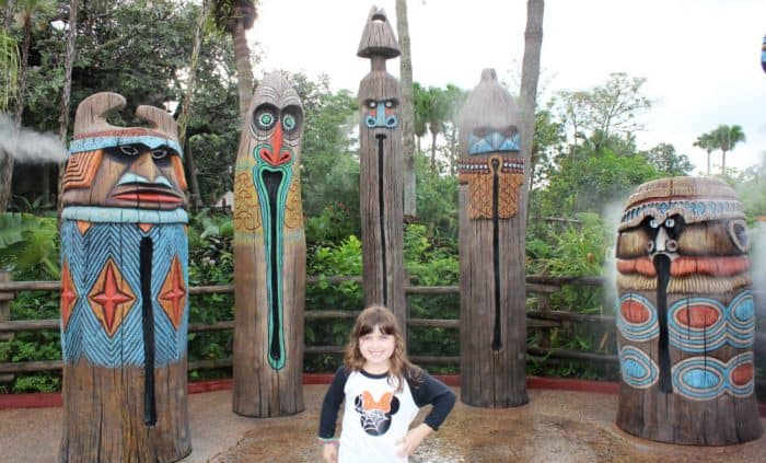Little girl in front of 5 tiki torches that mist water in Magic Kingdom