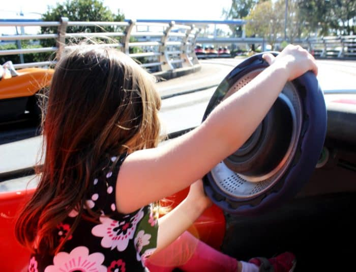 Toddler steering the wheel in a red Tomorrowland Speedway car along the track at Magic Kingdom