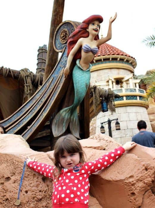 Toddler in red hoodie with white polka dots leaning against the rocks with the mermaid Ariel posing above her