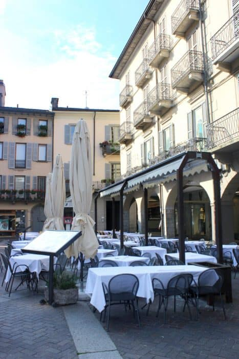 Tables and chairs are set out for a restaurant in a piazza awaiting the first customers