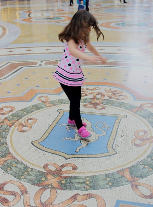 Kids in Milan love to spin on the bulls balls in the Galleria