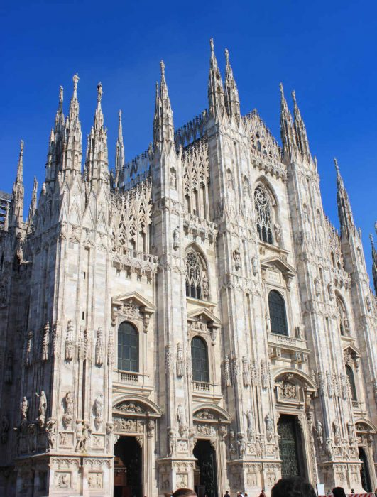 Side angle of Milan Duomo in front of a deep blue sky