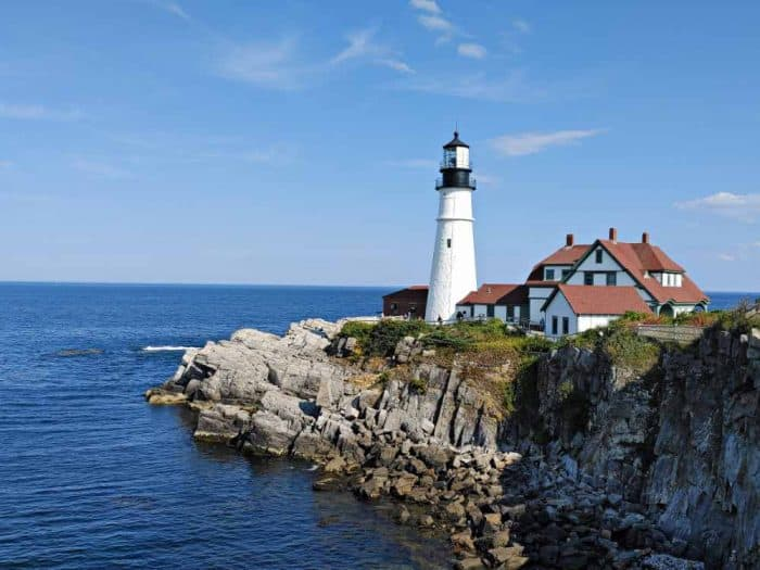 Rocky cliff on the edge of water with a tall, white lighthouse and and white building structure with brown roof.
