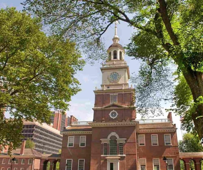 Stately orange brick building with a clock and bell tower framed between two large trees in Philadelphia, Pennsylvania.