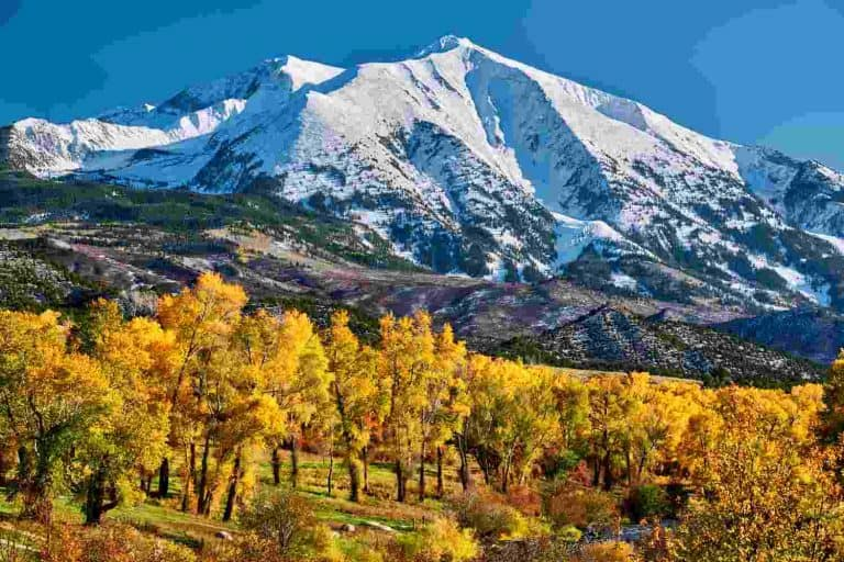 Snow capped rocky mountain range with golden aspen at the foot of the mountain