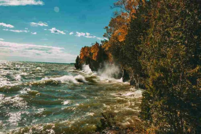 Waves crashing against a rocky shoreline cliff in Wisconsin.