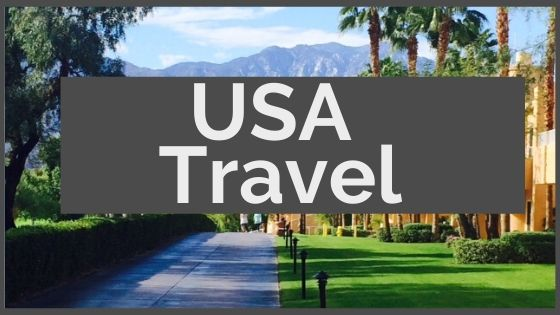 White text on top of gray box that reads USA Travel; on top of a picture with blue sky, mountains and green grass