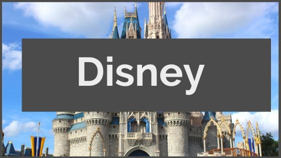 White text on gray box reading Disney over top of Cinderella's castle with blue turrets and white fluffy clouds in blue sky