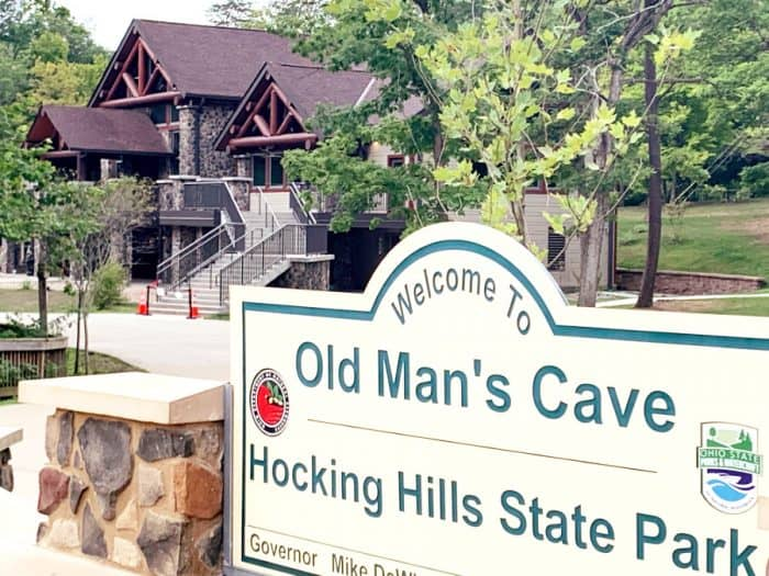 Stone and wooden 2 story building in background with a sign in front reading Welcome to Old Man's Cave Hocking Hills State Park