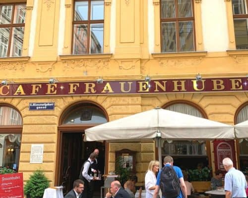 Yellow building with deep red and gold sign saying Cafe Frauenhuber; Tables and chairs set up under large umbrellas with people eating