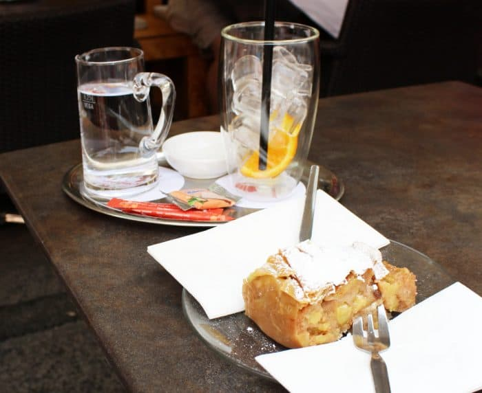 Silver platter with 2 red packets of sugar, a glass mug of water, and a glass filled with ice cubes and an orange slice along with a silver platter with a piece of apple strudel topped with whipped cream and a fork.