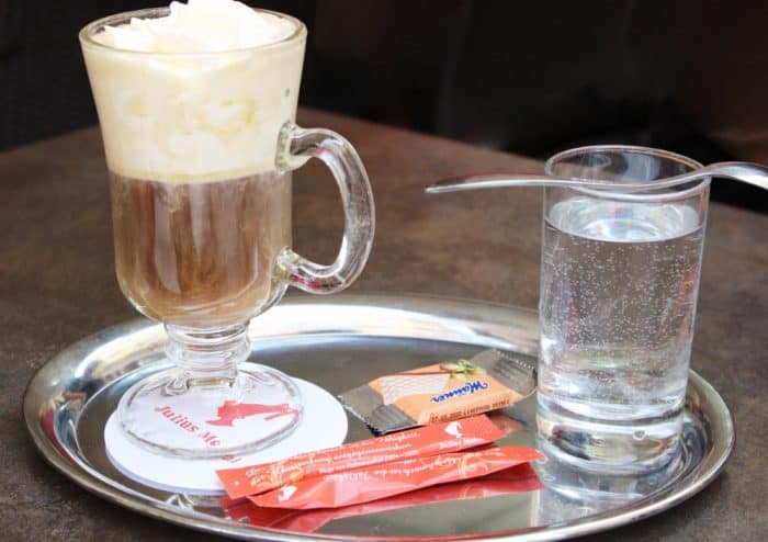 Silver platter with 2 red packets of sugar, a glass of water with spoon, a small wafer in brown and orange wrapper and a glass mug of coffee topped with whipped cream