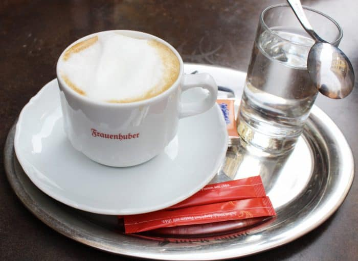 Silver platter with 2 red packets of sugar, a glass of water with spoon, and a white ceramic mug of coffee topped with foam