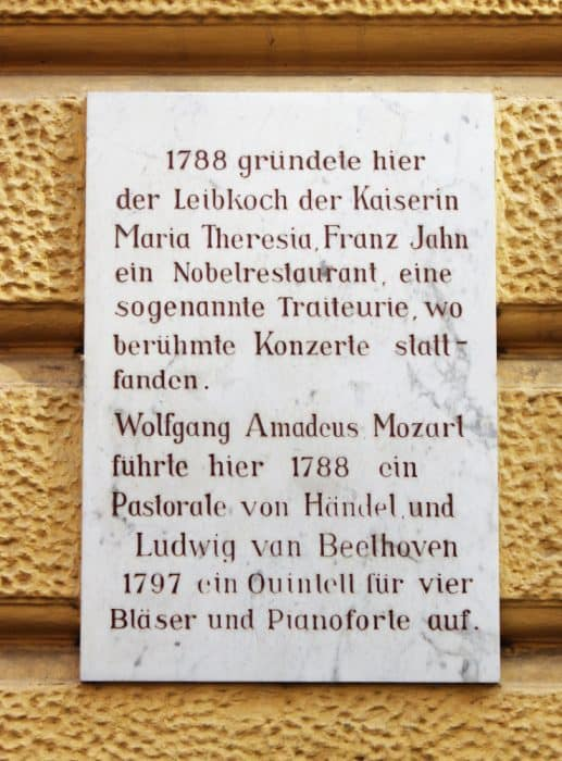 Marble stone with black German text on a yellow stucco wall