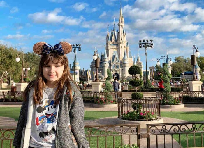 Young girl with rose gold minnie mouse ears on to match her outfit for Disney in front of Cinderella's castle.